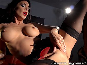 horny brown-haired Jessica Jaymes thumbs her delicious cooch pie in her office